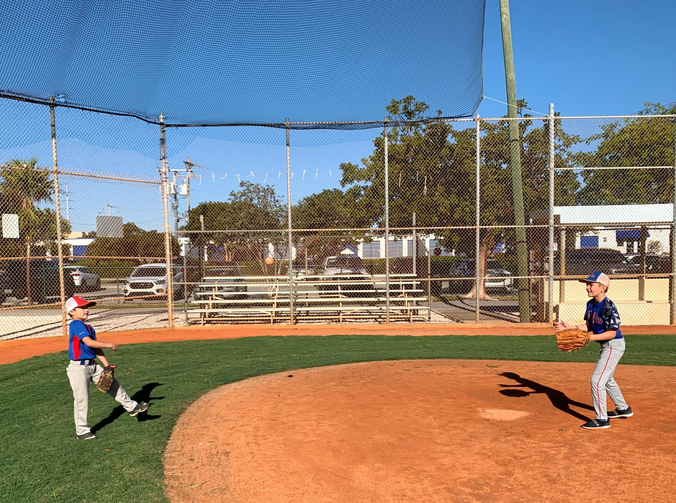 Two Upper Keys Little League players throw a ball to each other on the newly refurbished clay