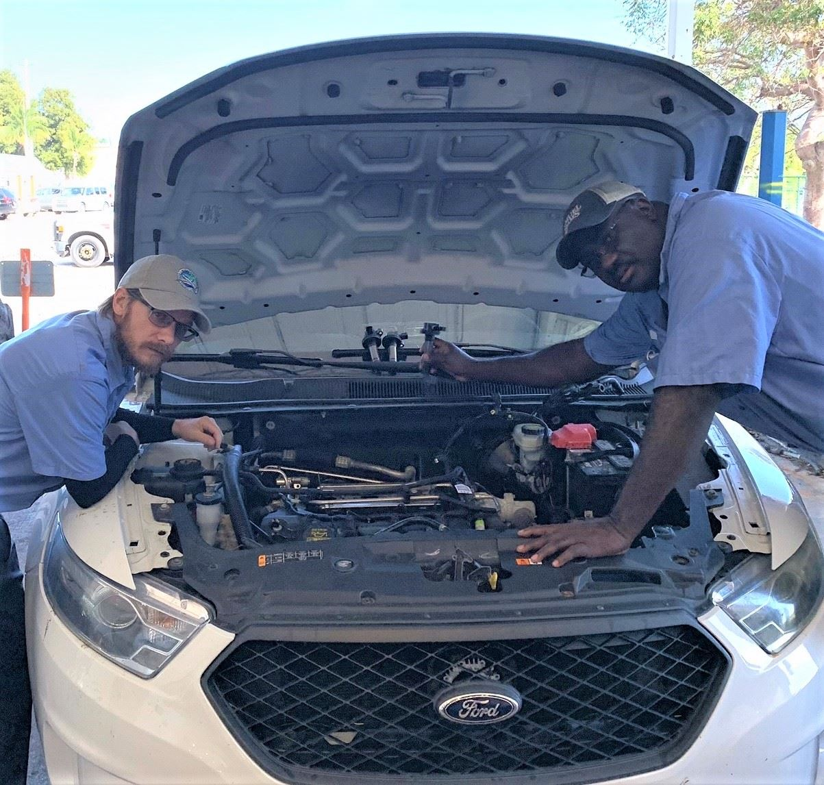 J Faulkner and Dean Steele look inside the hood of a white Ford car