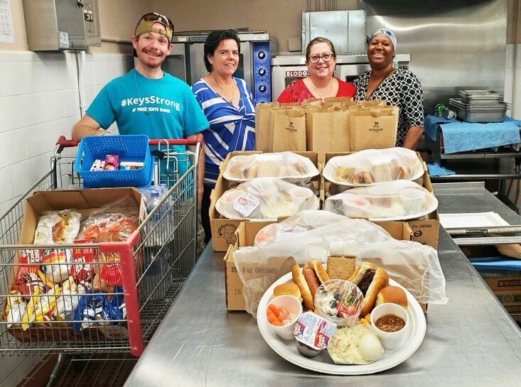 Volunteers prepare food for homebound residents on July 4.